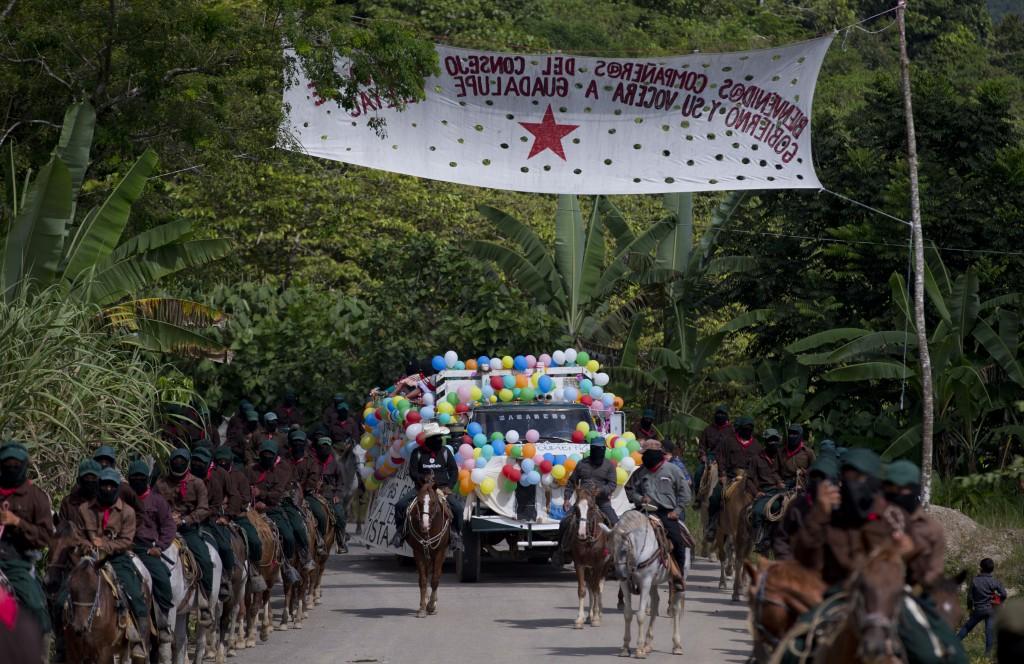 In this Saturday, Oct. 14, 2017 photo, horse riding members of the Zapatista National Liberation Army (EZLN) escort Maria de Jesus Patricio, president...