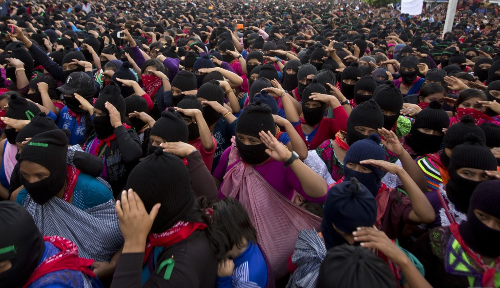 In this Monday, Oct. 16, 2017 photo, Zapatistas salute during the playing of Mexico's national anthem at a campaign rally for Maria de Jesus Patricio,...