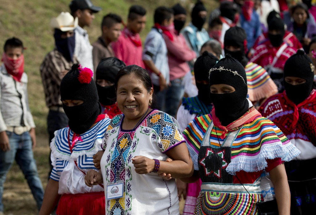 In this Saturday, Oct. 14, 2017 photo, masked women escort Maria de Jesus Patricio, presidential candidate for the National Indigenous Congress, as sh...