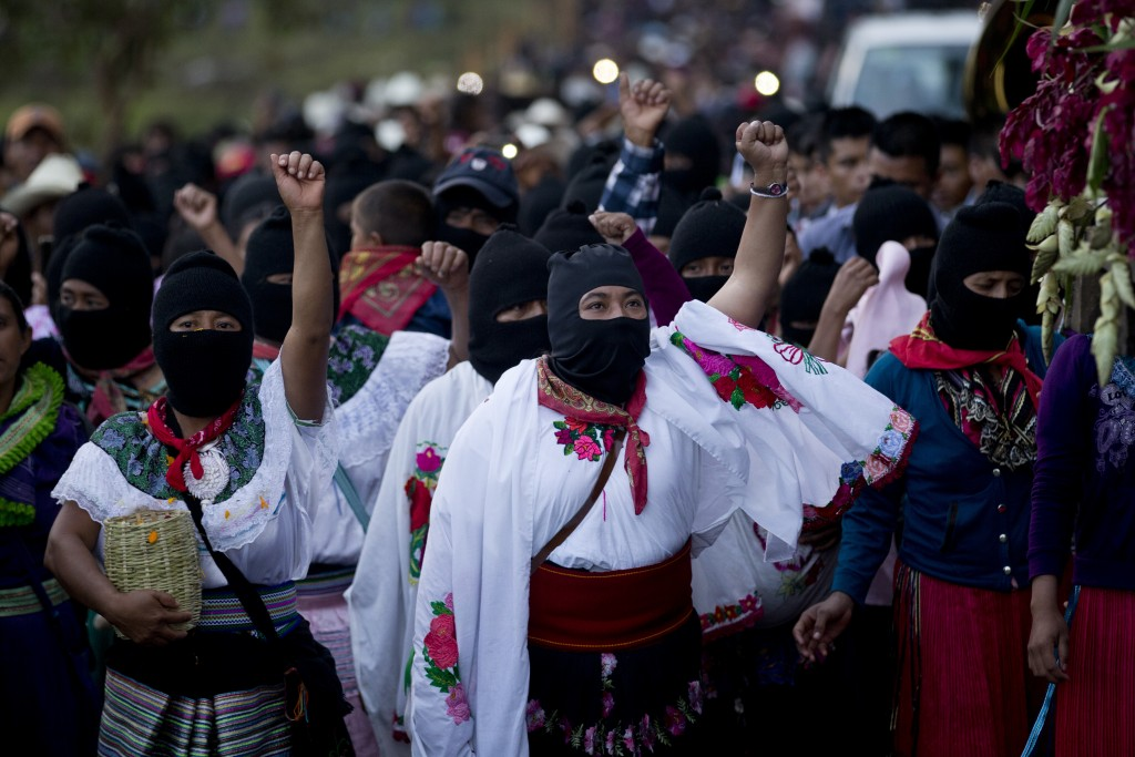 In this Sunday, Oct. 15, 2017 photo, masked indigenous women raise their fists to show support for Maria de Jesus Patricio, presidential candidate for...