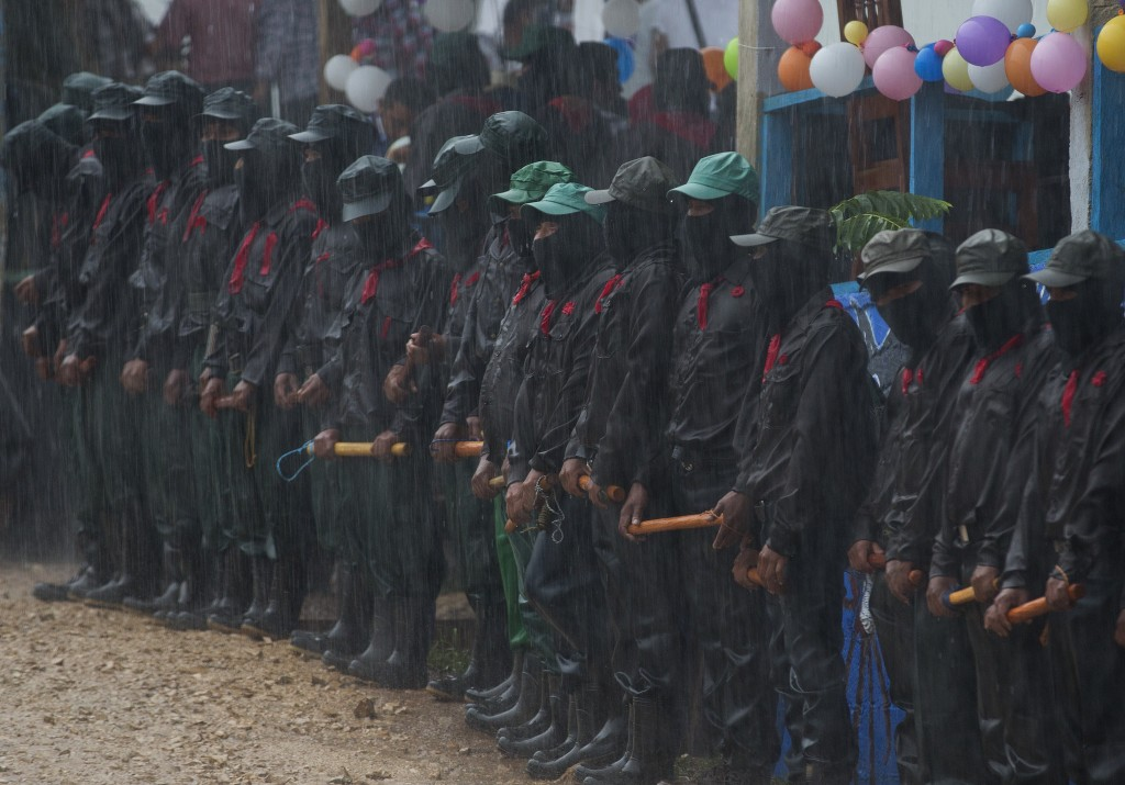 In this Monday, Oct. 16, 2017 photo, members of the Zapatista National Liberation Army (EZLN) stand in the pouring rain as they provide security durin...