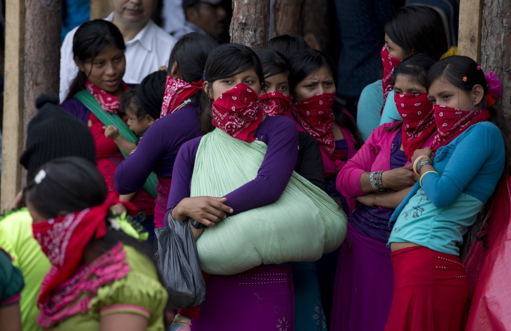 In this Saturday, Oct. 14, 2017 photo, masked indigenous women, one holding a child in a sling, wait for Maria de Jesus Patricio, presidential candida...