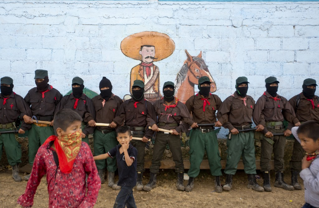 In this Monday, Oct. 16, 2017 photo, members of the Zapatista National Liberation Army (EZLN) provide security for a campaign rally by presidential ca...