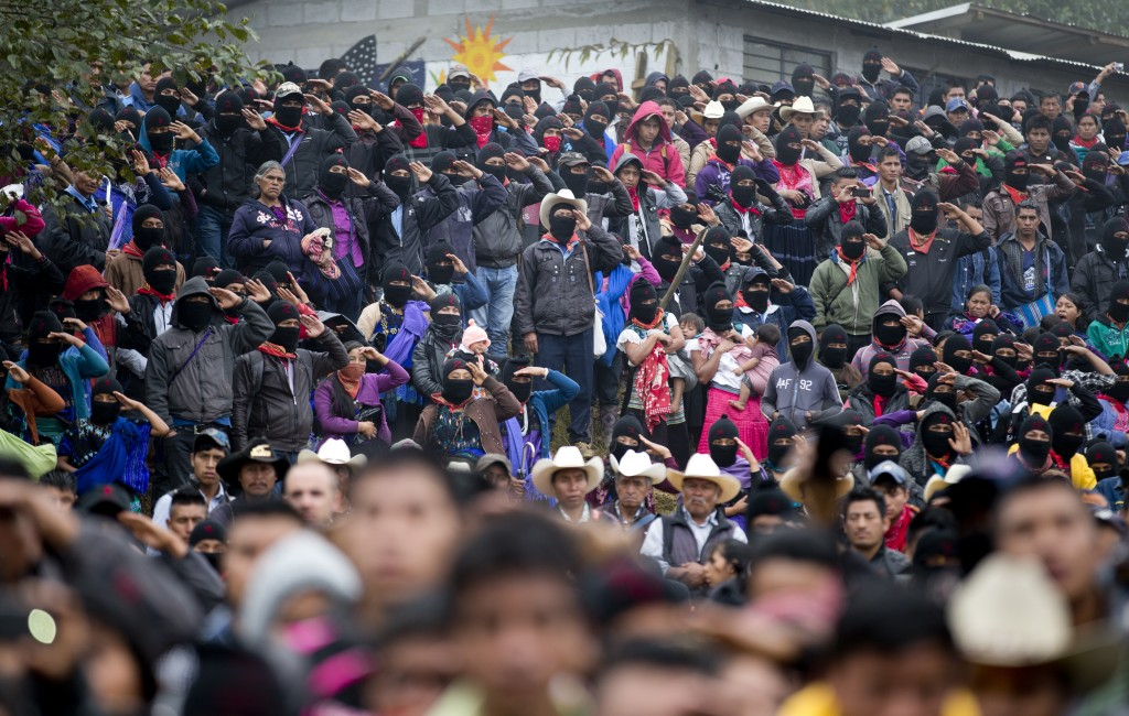 In this Thursday, Oct. 19, 2017 photo, Zapatistas salute during the playing of Mexico's national anthem at a campaign rally for Maria de Jesus Patrici...