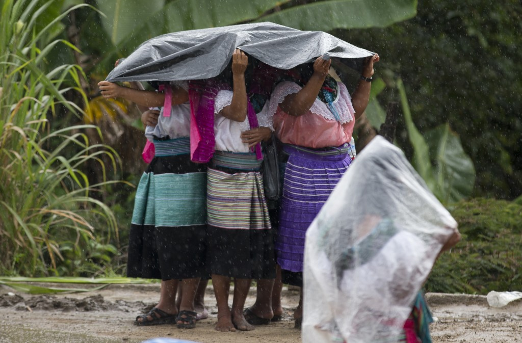 In this Sunday, Oct. 15, 2017 photo, indigenous women cover themselves in the rain as they wait for the arrival of Maria de Jesus Patricio, presidenti...