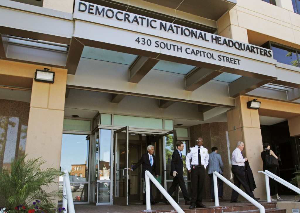 FILE - In this June 14, 2016 file photo, people stand outside the Democratic National Committee headquarters in Washington. Hackers tried to break int...