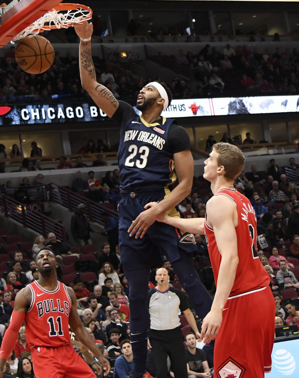 New Orleans Pelicans forward Anthony Davis (23) dunks the ball as Chicago Bulls guard David Nwaba (11) and forward Lauri Markkanen (24) watch during t...