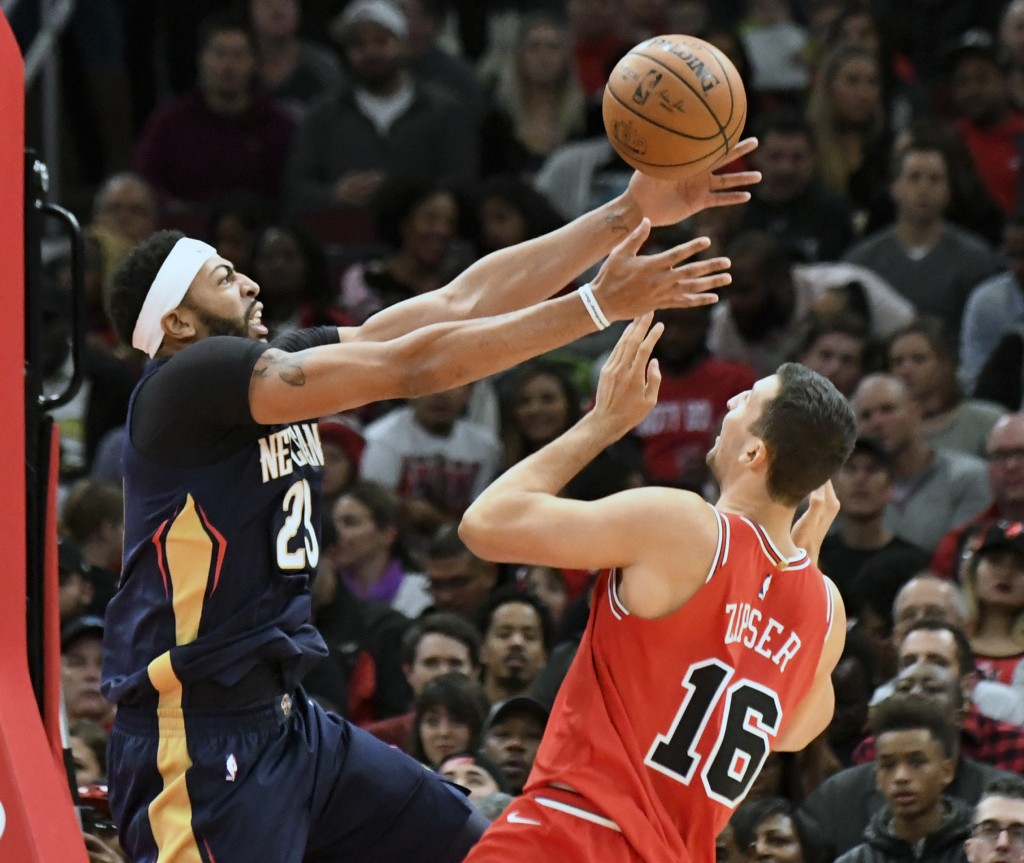 New Orleans Pelicans forward Anthony Davis (23) and Chicago Bulls forward Paul Zipser (16) go for the ball during the first half of an NBA basketball ...