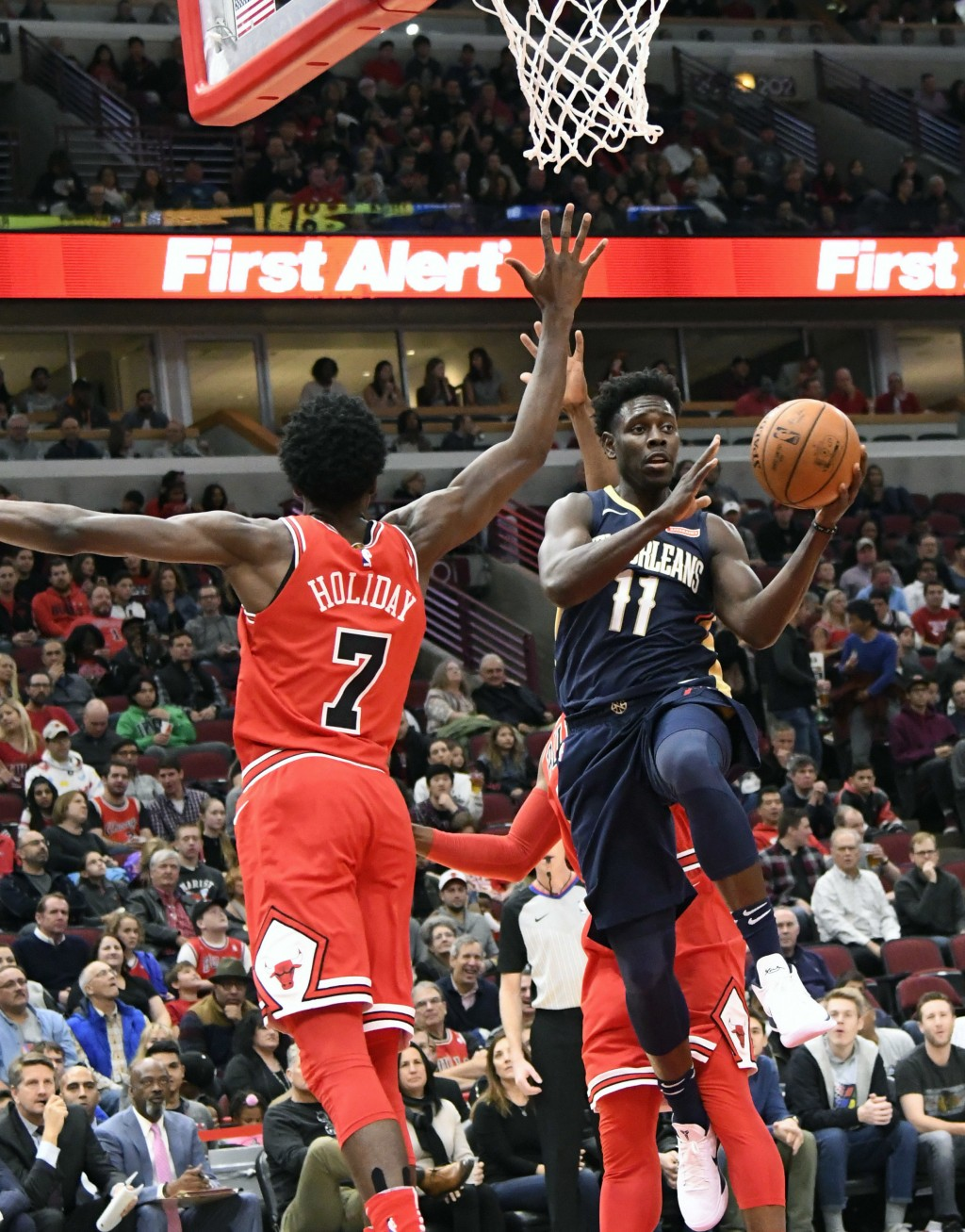 New Orleans Pelicans guard Jrue Holiday (11) looks to pass the ball around Chicago Bulls guard Justin Holiday (7) during the first half of an NBA bask...