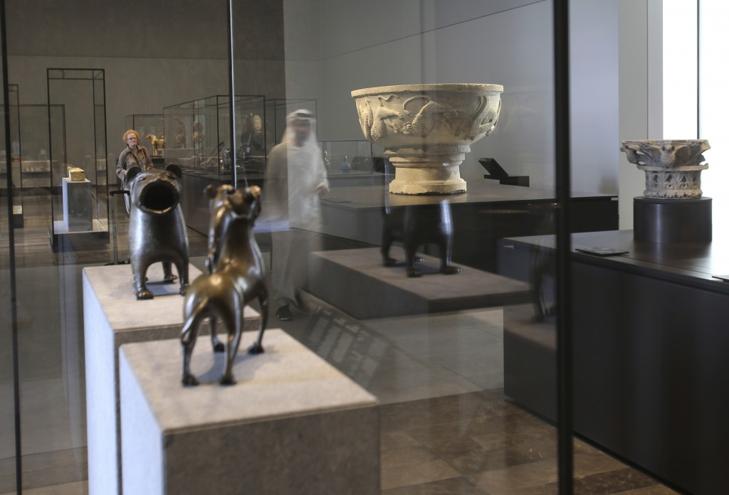 In this Monday, Nov. 6, 2017, photo, a man passes by a basin inscribed with the name of Bonifilius from north of Italyat the Louvre Abu Dhabi, United ...