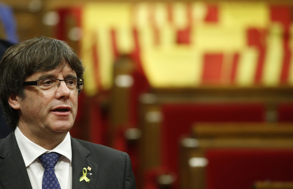 FILE - This is a Friday, Oct. 27, 2017 file photo of Catalan President Carles Puigdemont chants the Catalan anthem after a vote on independence in the...