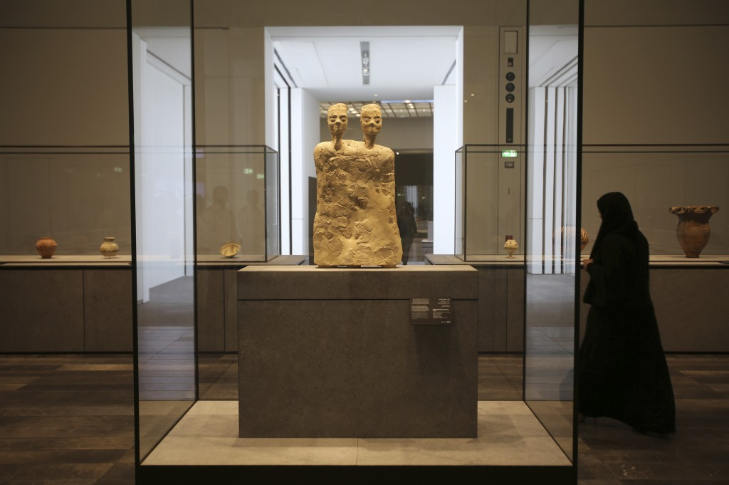 "In this Monday, Nov. 6, 2017, photo, an Emirati woman passes by ""Monumental Statue with two heads"" from Jordan about 6500 BCE, at the Louvre Abu Dhabi"