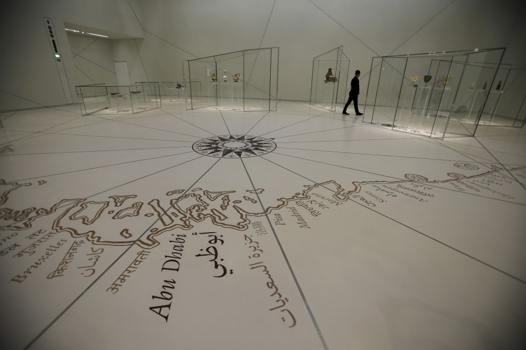 In this Monday, Nov. 6, 2017 photo, a man walks at a gallery of the Louvre Abu Dhabi, United Arab Emirates. The Louvre Abu Dhabi is preparing its gran...