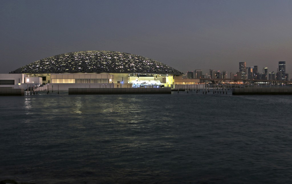 In this Monday, Nov. 6, 2017, photo, the night view of Louvre Abhu Dhabi is seen in front of the city skyline in Abu Dhabi, United Arab Emirates. The