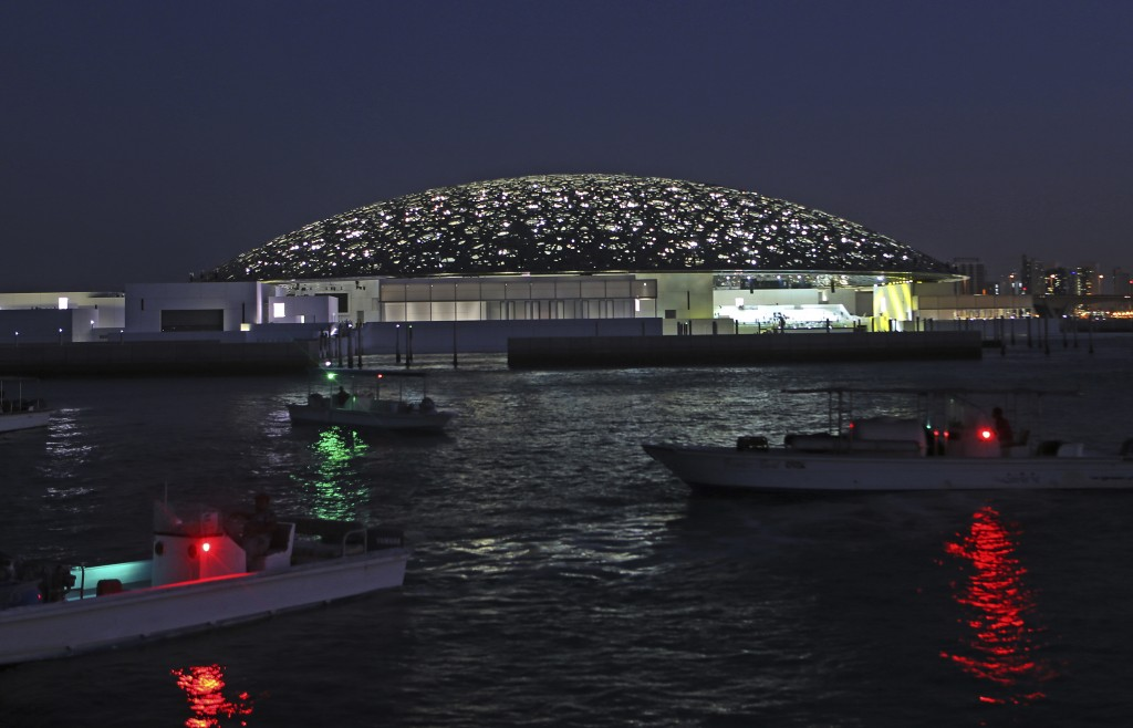 In this Monday, Nov. 6, 2017, photo, boats lights are reflected on the water in front of the Louvre Abu Dhabi, United Arab Emirates. The Louvre Abu Dh
