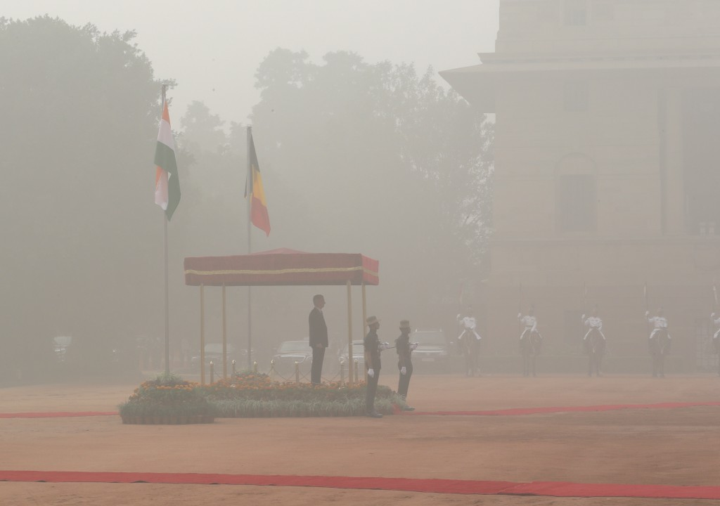 Belgium's King Philippe inspects a military guard of honor, surrounded by smog, at the Indian Presidential palace in New Delhi, India, Tuesday, Nov. 7