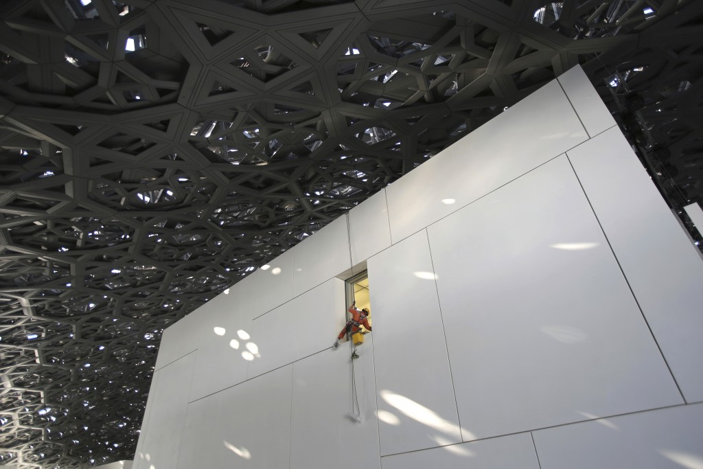 In this Monday, Nov. 6, 2017, photo, a worker cleans a window under the dome of the Louvre Abu Dhabi, United Arab Emirates. The Louvre Abu Dhabi is pr