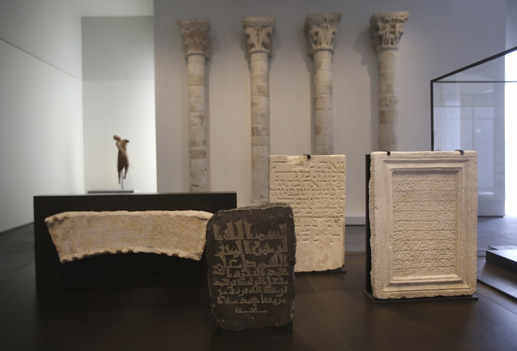 In this Monday, Nov. 6, 2017, photo, a variety of funerary steles from Christian, Jewish and Muslim faiths are seen at the Louvre Abu Dhabi, United Ar...