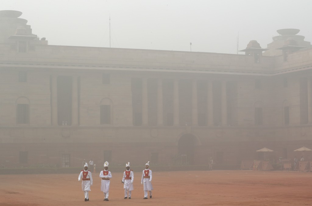 Indian presidential staff members walk surrounded by smog at the presidential palace in New Delhi, India, Tuesday, Nov. 7, 2017. Air pollution in Indi