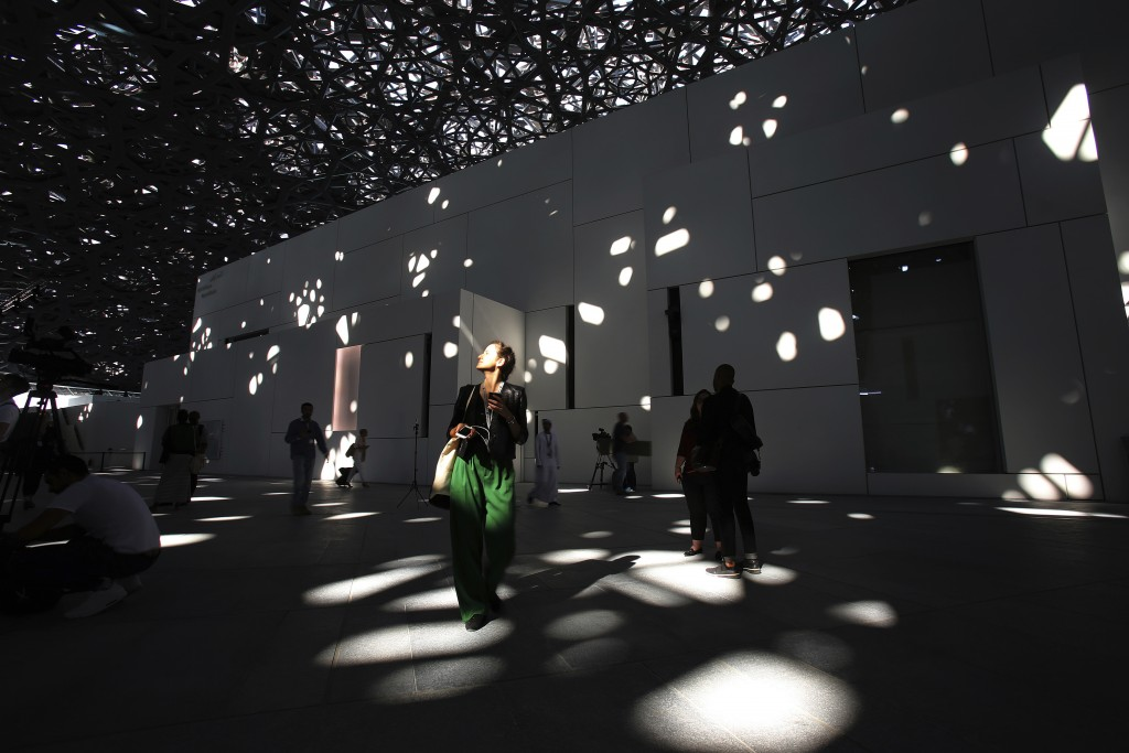 In this Monday, Nov. 6, 2017, photo, a journalist walks under the lights coming through of the dome at the Louvre Abu Dhabi, United Arab Emirates. The...