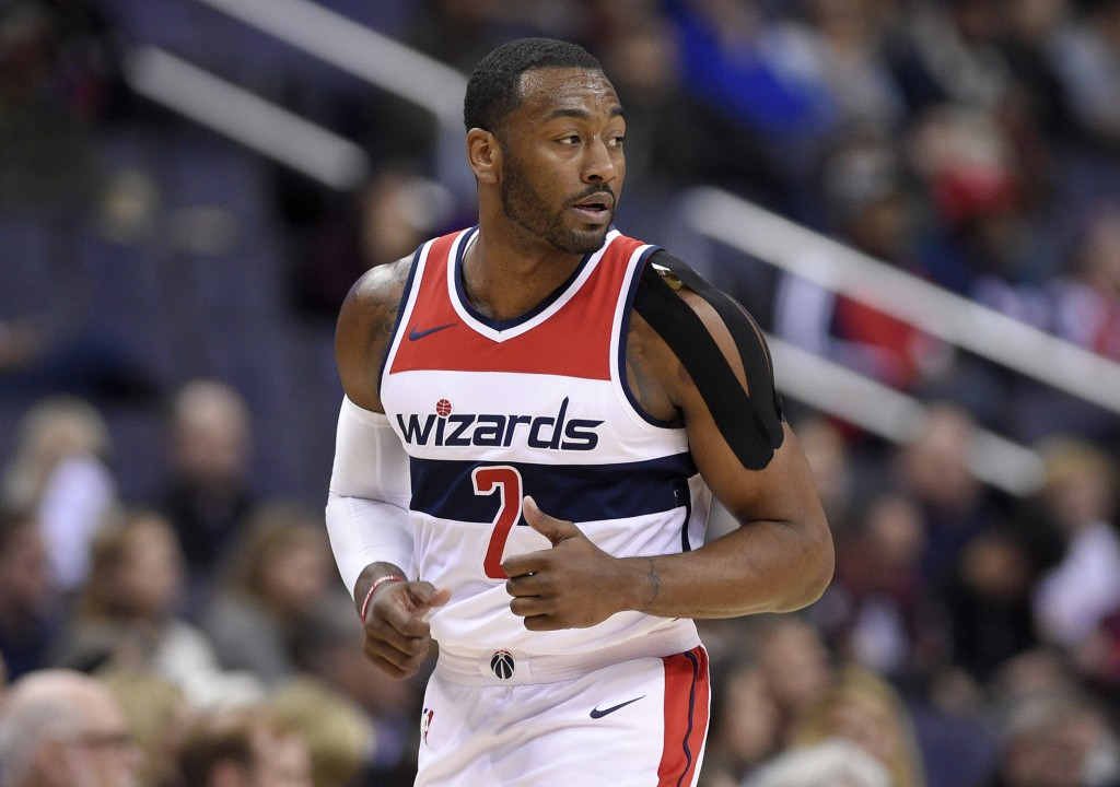 Washington Wizards guard John Wall (2) runs down the court with a heavily taped shoulder during the first half of an NBA basketball game against the D...