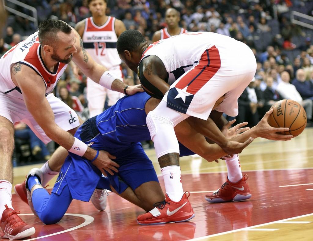 Washington Wizards center Marcin Gortat, left, of Poland, and Washington Wizards guard John Wall, right, battle for the ball against Dallas Mavericks