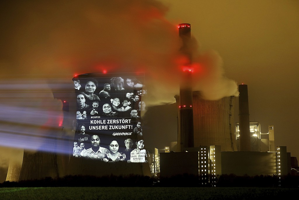 "Greenpeace activists project the writing ""Coal destroys our future"" on the cooling tower of the lignite power plant Neurath near Grevenbroich, western..."