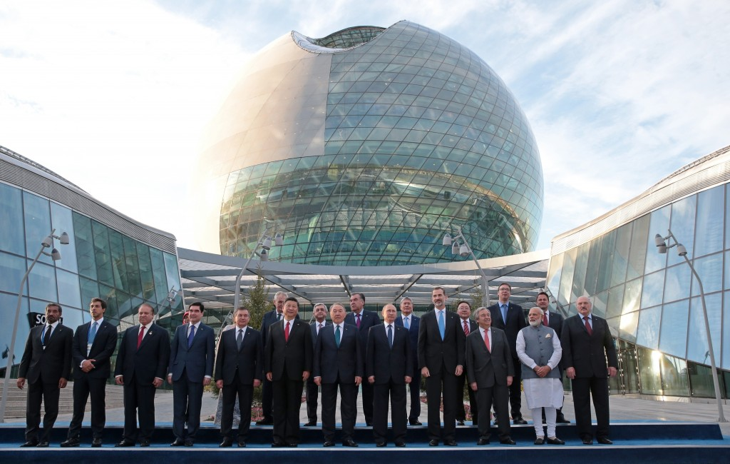 FILE - In this June 9, 2017, file photo, world leaders, including Russian President Vladimir Putin, center, pose for a photo with others as they atten...