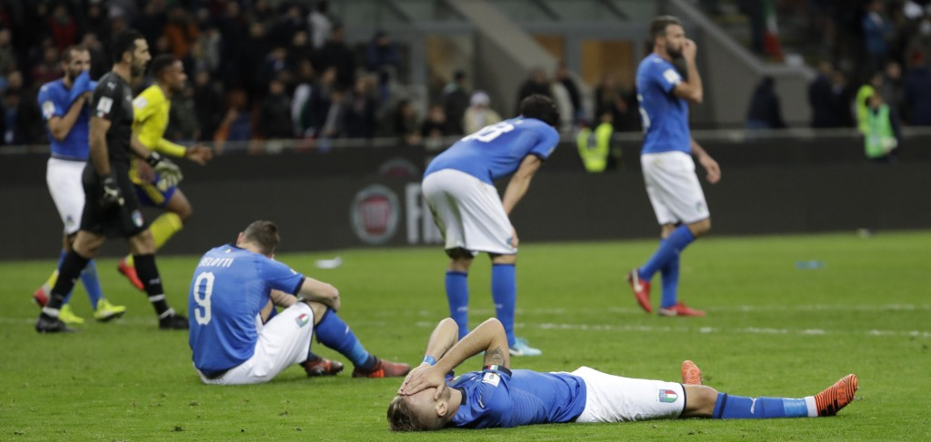 Italy's Ciro Immobile, foreground, and Italy's Andrea Belotti, seated left, react to their team's elimination in the World Cup qualifying play-off sec