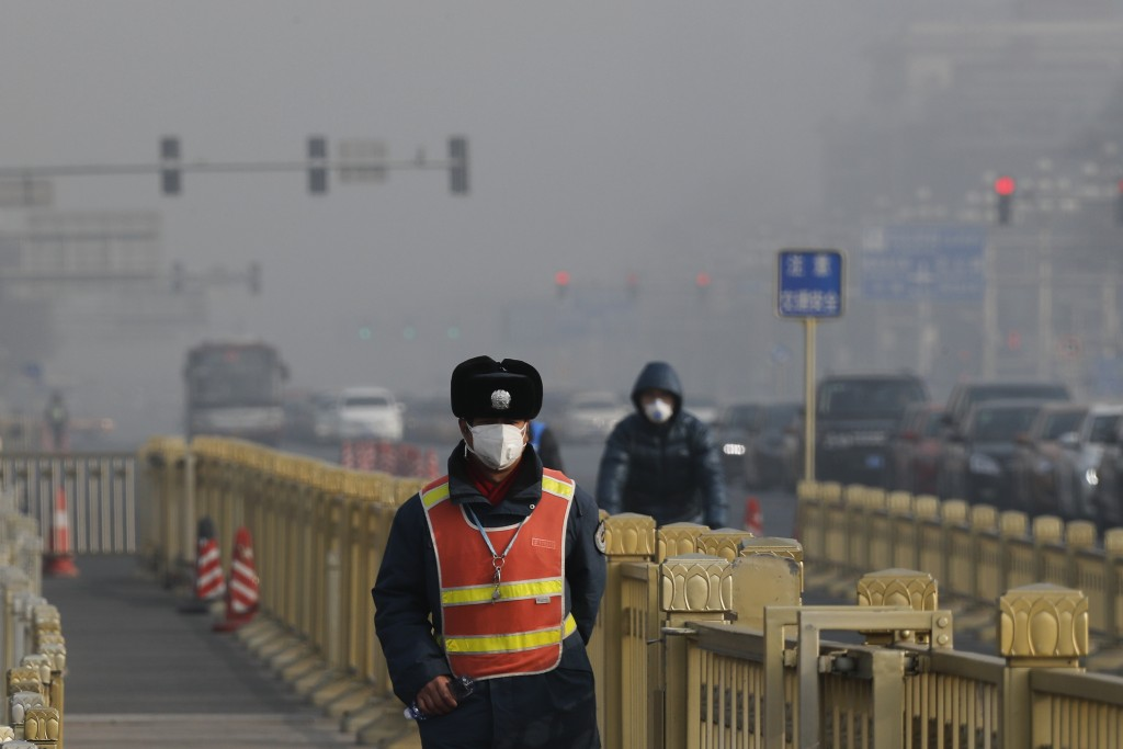 FILE - In this Jan 4, 2017 file photo a traffic warden wearing a protection mask walks on a street near Tiananmen Square in Beijing as the capital of
