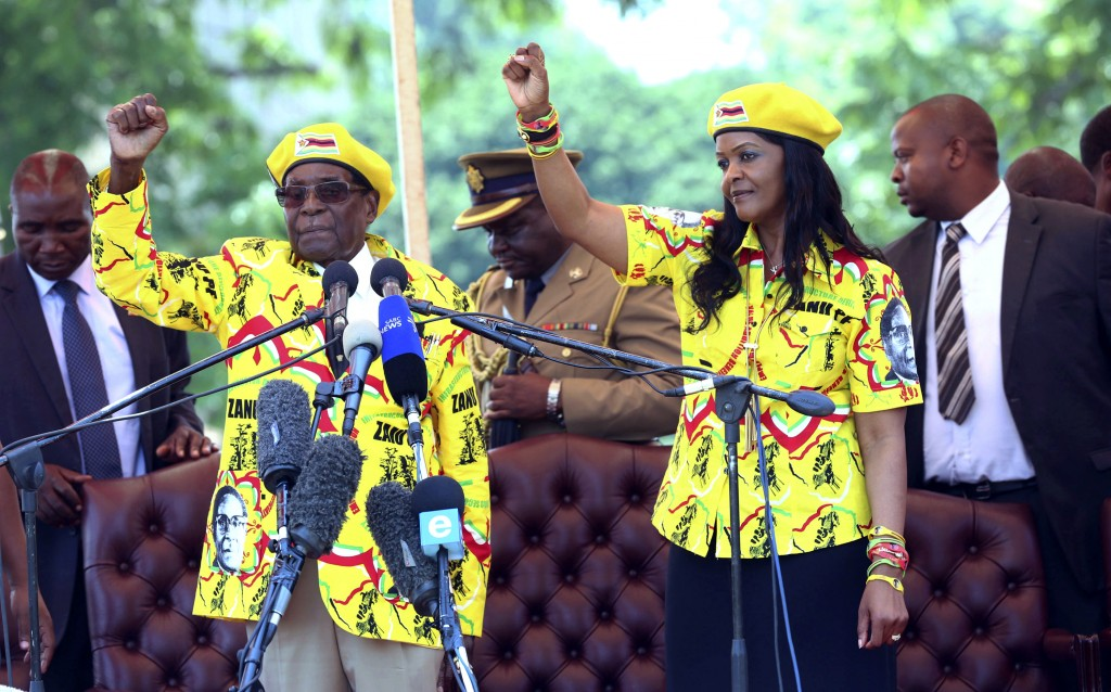 FILE - In this Wednesday, Nov. 8, 2017 photo, Zimbabwe's President Robert Mugabe, left, and his wife Grace chant the party's slogan during a solidarit...