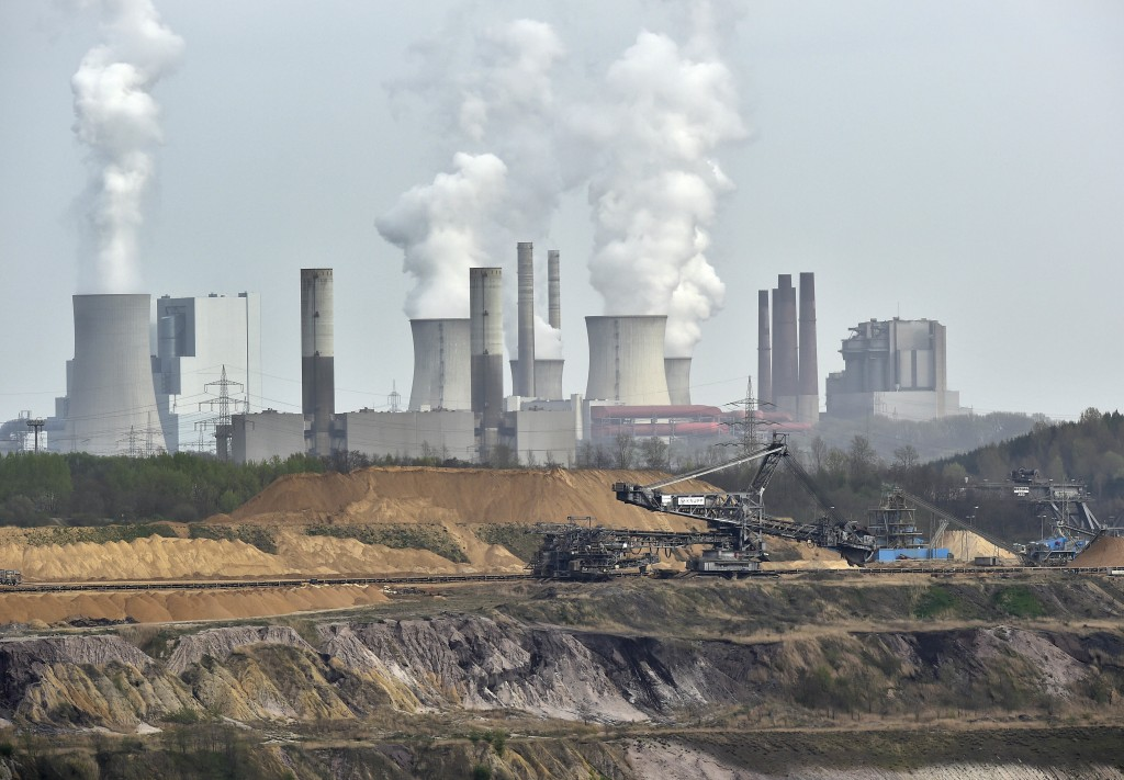 FILE - In this April 3, 2014 file photo giant machines dig for brown coal at the open-cast mining Garzweiler in front of a power plant near the city o