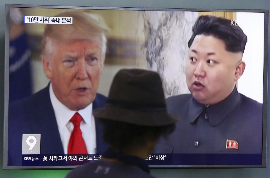 FILE - In this Aug. 10, 2017, file photo, a man watches a TV screen showing U.S. President Donald Trump and North Korean leader Kim Jong Un, right, du