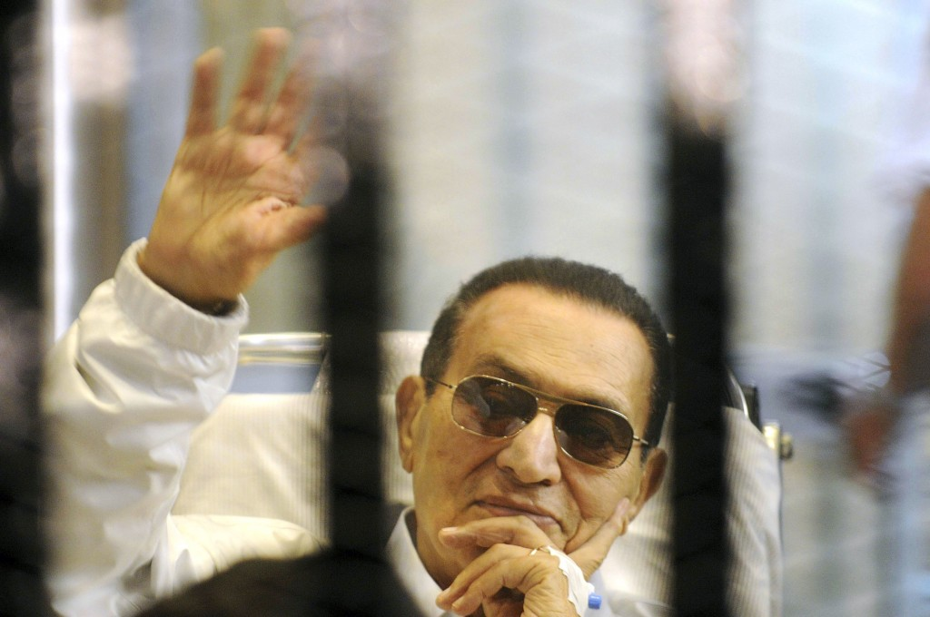FILE - In this Saturday, April 13, 2013 file photo, former Egyptian President Hosni Mubarak waves to his supporters from behind bars as he attends a h...