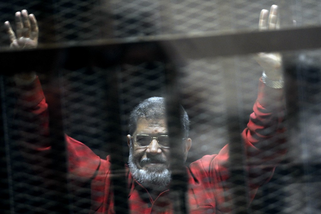 FILE - In this June 21, 2015 file photo, former Egyptian President Mohammed Morsi, wearing a red jumpsuit that designates he has been sentenced to dea...