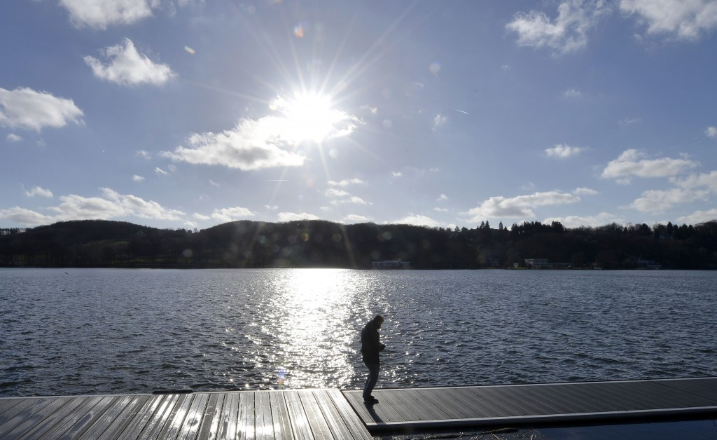 FILE - In this Jan 28, 2014 file photo man enjoys the winter sun at the Baldeney lake in Essen, Germany.  Lake Baldeney has become a symbol for the ef