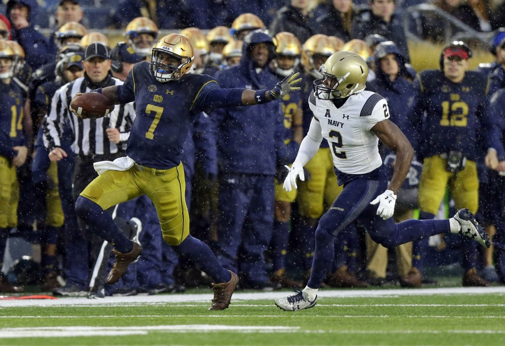 Notre Dame quarterback Brandon Wimbush (7) is chased by Navy safety Jarid Ryan (2) during the first half of an NCAA college football game in South Ben...