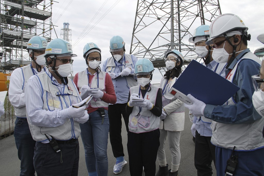 In this Oct. 12, 2017, photo, a group of foreign journalists are seen in low-dose gear during their visit to the tsunami-hit Fukushima Dai-ichi nuclea