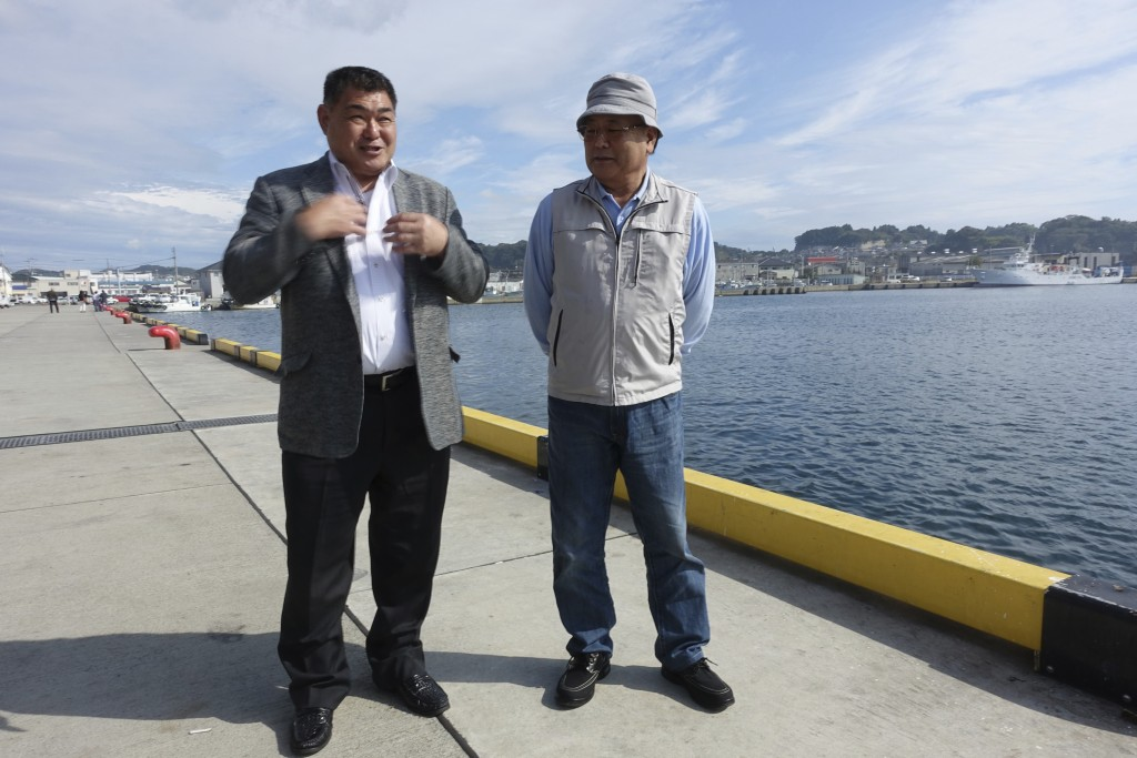 In this Oct. 12, 2017, photo, local fishermen Yuichi Manome, an abalone grower, left, and Fumio Haga, a coastal drag-net operator, discuss their conce