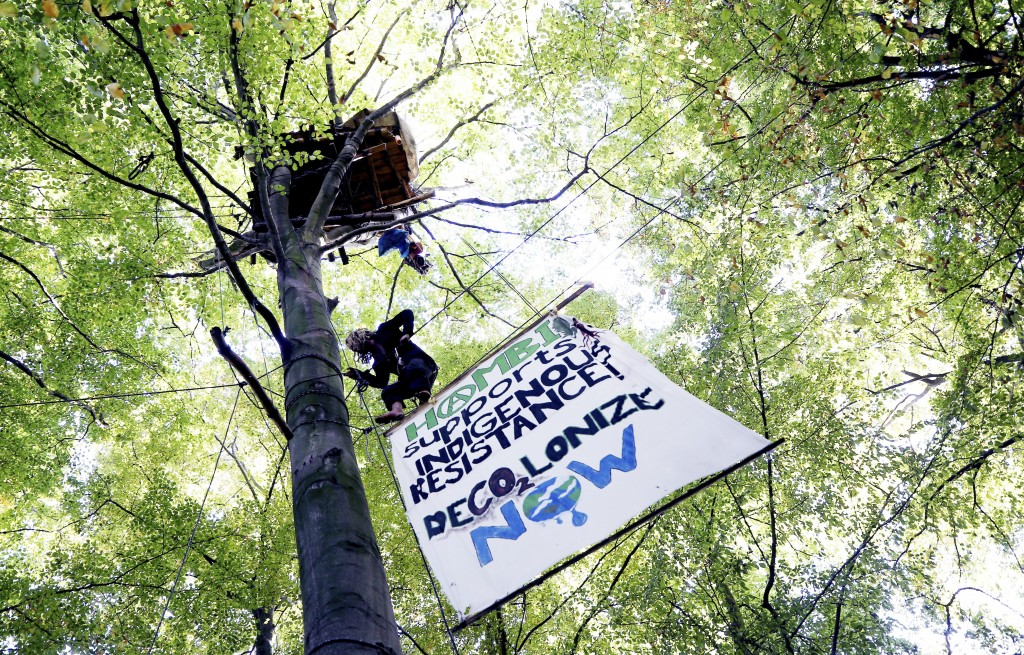 FILE - In this Oct. 15, 2017 file photo an activist climbs up a tree at the Hambach forest near Morschenich, Germany. Cologne's administrative court r