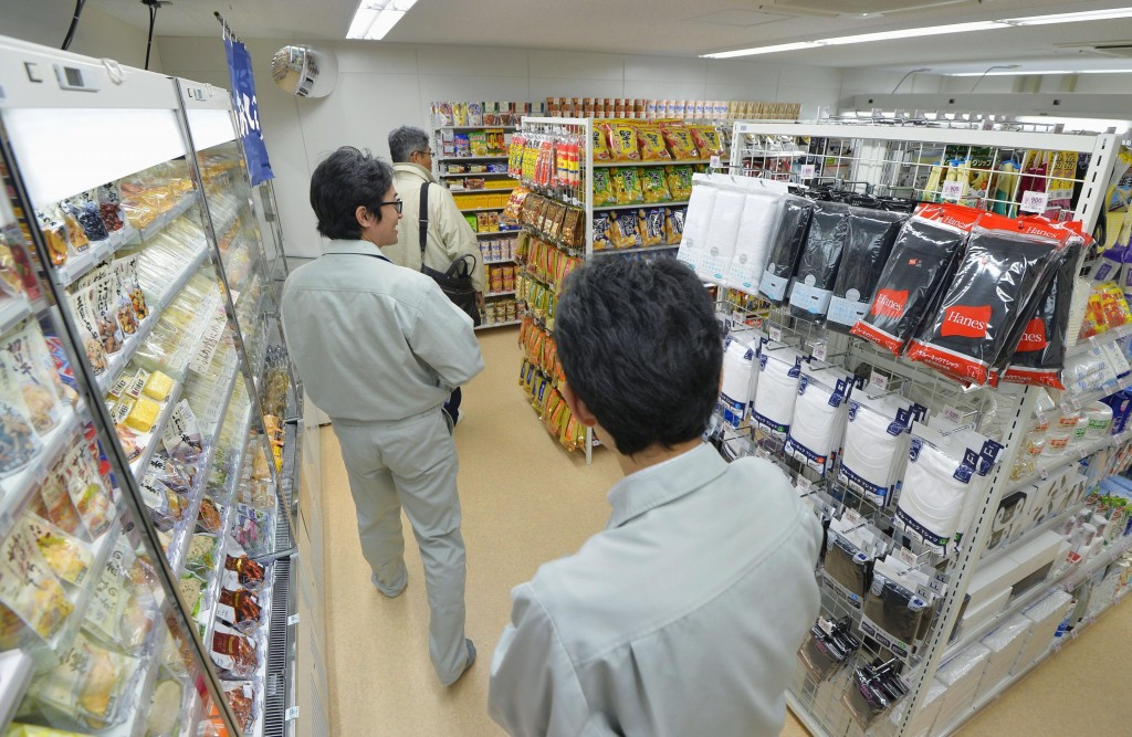 In this March 1,  2016 photo, workers shop at a convenience store in the compound of Fukushima Dai-ichi nuclear plant in Okuma, Fkushima prefecture. T