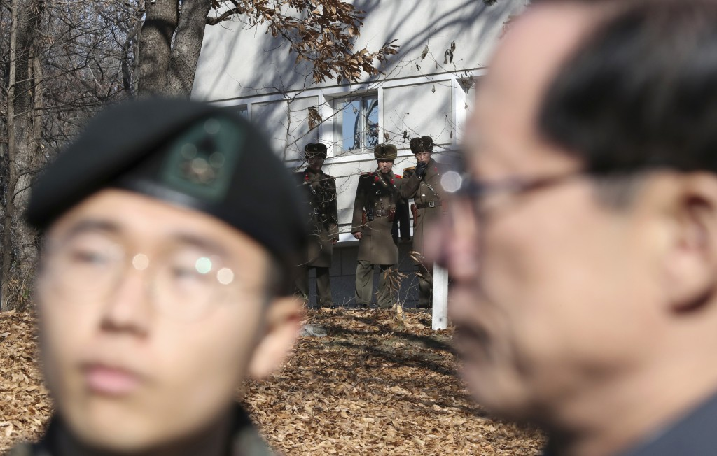 Three North Korean soldiers, back, look at the South side near the spot where a North Korean soldier crossed the border on Nov. 13, as South Korean De...