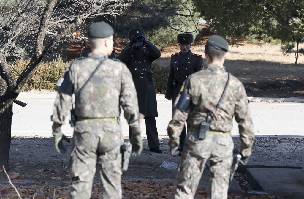 Three North Korean soldiers, background, look at the South side as two South Korean soldiers stand guard at the spot where a defector crossed the bord...