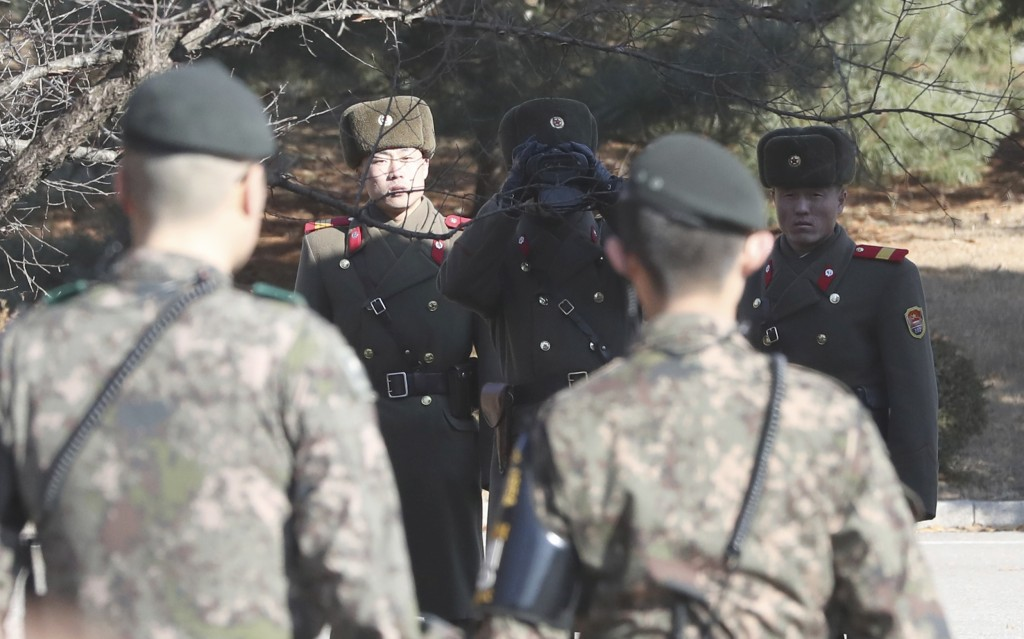 Three North Korean soldiers look at the South side as two South Korean soldiers stand guard at the spot where a defector crossed the border on Nov. 13...