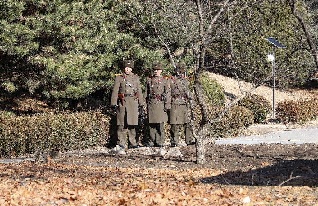 Three North Korean soldiers look at the South side at the spot where a North Korean soldier crossed the border on Nov. 13, at the Panmunjom in the Dem...