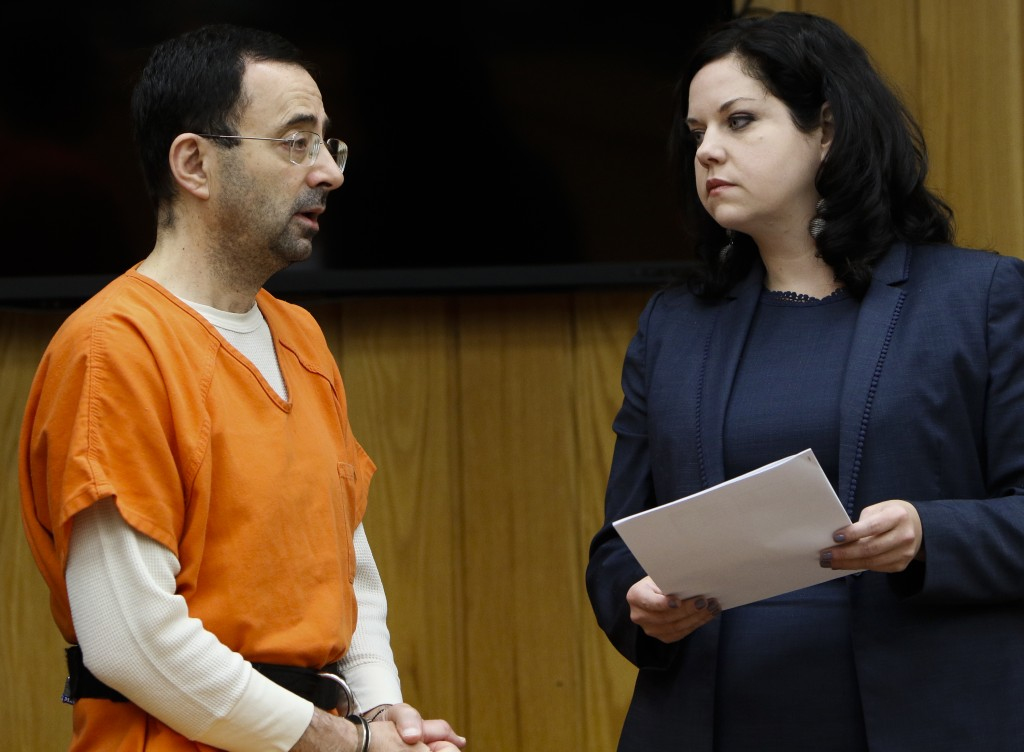 Former sports doctor Larry Nassar, left, stands with his attorney Shannon Smith as he pleads guilty to three counts of first-degree criminal sexual co