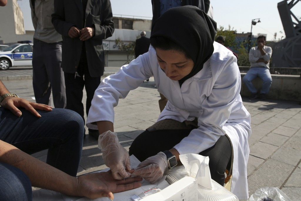 In this Monday, Nov. 6, 2017 photo, psychologist Atefeh Azimi, a member of Reviving Values aid group draws blood of a man for a free voluntary HIV tes...