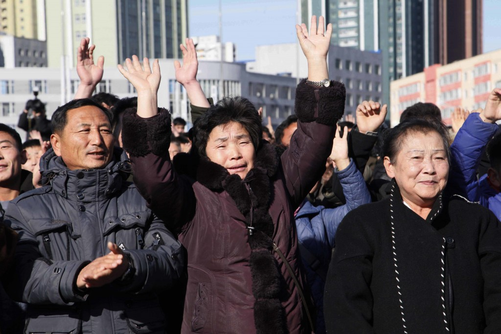 People cheer as they watch the news broadcast announcing North Korean leader Kim Jong Un's order to test-fire the newly developed inter-continental ba