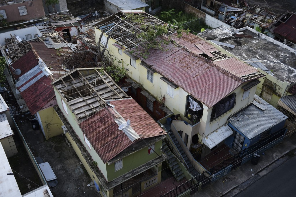 In this Nov. 15, 2017 photo, some roofs damaged by the whip of Hurricane Maria are shown still exposed to rainy weather conditions, in San Juan, Puert...