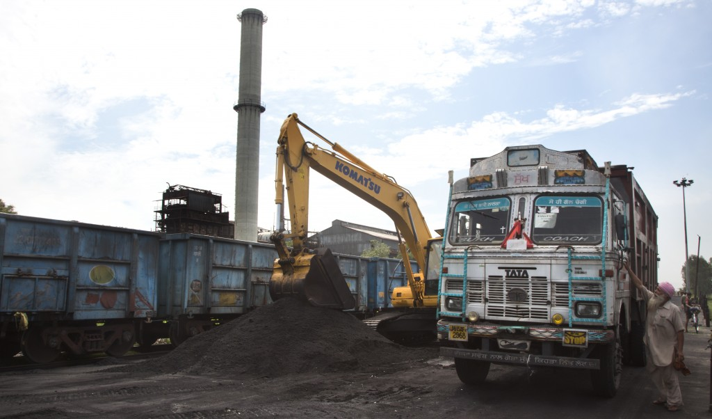 In this July 14, 2017 photo, domestically produced petroleum coke is loaded onto a truck to be transported to factories, at a railway station in Rampu...